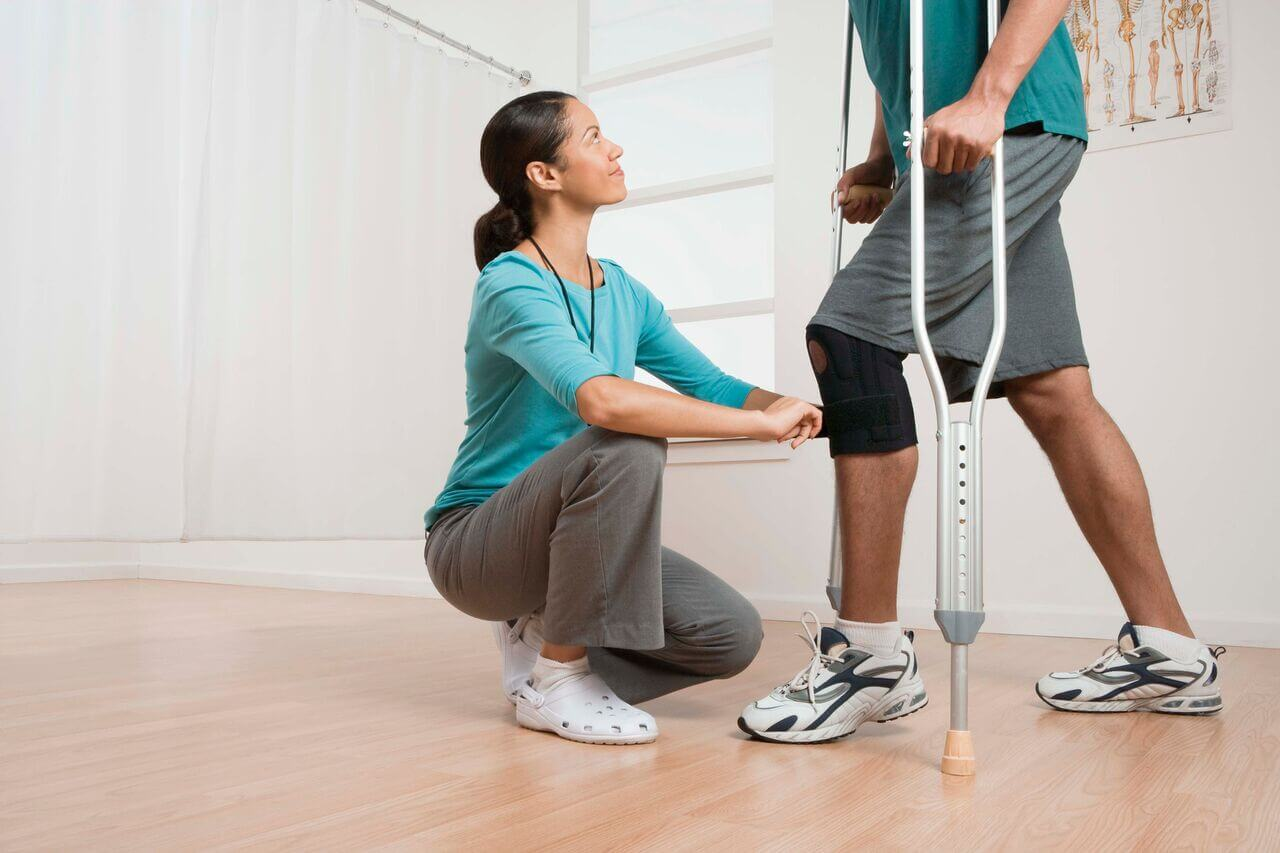 Image of a woman with a man in crutches
