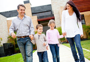 Happy family walking outside their home and smiling