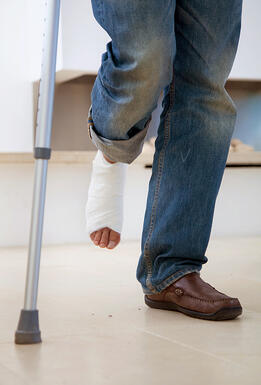 Man with a cast on his leg and crutches